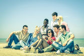 Group of young hipster best friends with digital tablet sitting at the beach - Concept of multi cultural friendship against racism - Interaction with new trends and technologies devices in open spaces — Stock Photo