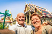 Senior happy couple taking a selfie at Grand Palace temples in Bangkok - Thailand adventure travel to asian destinations - Concept of active elderly and fun around the world with new technologies — ストック写真