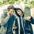 Young hipster brothers having fun with smartphone - Best friends sharing free time with new trends technology - Guys enjoying everyday life moments texting connected with modern smart phone device — Stock Photo #64498639