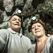 Senior happy couple taking a selfie at the entrance of Tham Phu Kham in Vang Vieng - Adventure travel in Laos and asian destinations - Concept of active elderly around the world with new technologies — Stock Photo #64499603
