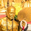 Golden statue of old buddhist monk with flowers ring in the sanctuary of Doi Suthep - Ancient buddha temple in Chiang Mai province in Thailand - Concept of faith and religion in asian countries — Stock Photo #64499713