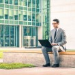 Young hipster business man sitting with laptop at business center - Modern concept of technology wifi connection - Handsome businessman working outdoors with computer connected with wirless internet — Stock Photo #64566135