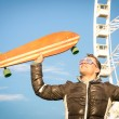 Young hipster man with longboard skate board at luna park - Concept of modern vintage alternative lifestyle with handsome guy at ferris wheel - Spring youth alternative fashion in a sunny happy day — Stock Photo #64566201