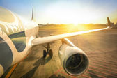 Airplane at terminal gate ready for takeoff - Modern international airport during sunset - Concept of emotional travel and wander around the world - Logo on aircraft body has been strongly modified — Stock Photo