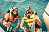 Senior happy couple using selfie stick in tropical sea excursion - Boat trip snorkeling in exotic scenarios - Concept of active elderly and fun around the world - Soft vintage filtered look — Stock Photo