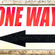 Vintage one way sign with black arrow showing the direction under red letters — Stock Photo #68520301