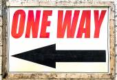 Vintage one way sign with black arrow showing the direction under red letters — Stock Photo
