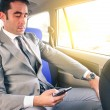 Young handsome businessman sitting in taxi cab while texting sms with smartphone - Business concept with modern man using smart phone - Soft vintage editing with artificial sunlight from the window — Stock Photo #68606993