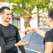 Happy satisfied young man receiving car keys after second hand sale - Concept business transport trade of modern luxury vehicles - Car rental assistance and insurance customer care — Stock Photo #68607051