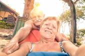 Senior happy couple taking selfie at in Thailand trip - Adventure concept of active elderly and fun around the world with new technologies - Warm saturated filtered look with soft focus on the woman — Stock Photo