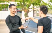 Happy satisfied young man receiving car keys after second hand sale - Concept business transport trade of modern luxury vehicles - Car rental assistance and insurance customer care — Stock Photo