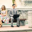 Couple in moment of disinterest - Break up concept and new technologies addiction - Business man at laptop ignoring girlfriend texting sms with smartphone - Neutral color tone due to the cloudy day — Stock Photo #68709235