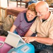 Happy senior couple sitting with digital laptop and travel baggage during adventure trip around the world - Concept of active elderly lifestyle and interaction with new trends and technologies — Stock Photo #68709237