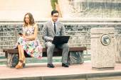 Couple in moment of disinterest  - Break up concept and new technologies addiction - Business man at laptop ignoring girlfriend texting sms with smartphone - Neutral color tone due to the cloudy day — Stock Photo