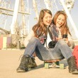 Best friends enjoying time together with smartphone music playlist in a spring sunny day - New trends and technology concept with hipster girlfriends having fun outdoors - Warm vintage filtered look — Stock Photo #68970213