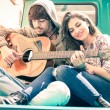 Romantic couple of lovers playing guitar on old fashioned mini car - Nostalgic retro concept of love with soft focus on the faces of boyfriend and girlfriend - Overexposed desaturated vintage filter — Stock Photo #68970237