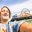 Handsome man taking a selfie at Santa Monica Pier with ferris wheel - Sunny day in California coast - Adventure travel lifestyle around United States of America - Composition with tilted horizon — Stock Photo #68970253