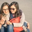 Best friends enjoying time together with smartphone in a spring sunny day - New trends and technology concept with hipster girlfriends having fun outdoors - Alternative four seasons fashion clothes — Stock Photo #68970271