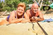 Senior happy couple taking selfie with stick in Thailand trip - Adventure concept of active elderly and fun around the world - Hot sunny day with real saturated light conditions — Stock Photo