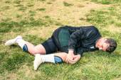 Soccer player injured during amateur football match - Concept of sport failure and physical accident — Stock Photo