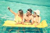 Best friends taking selfie at swimming pool with yellow airbed - Summer friendship concept with new trends and technology - Man and girlfriends with smartphone on a vintage overexposed filtered look — Stock Photo