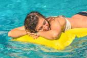 Beautiful young woman relaxing on a yellow inflatable mattress in clear blue water - Summer chilling out with girl in swimming pool at exclusive hotel resort — Stock Photo