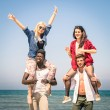 Multiracial best friends at beach having fun with piggyback game - Spring summer concept of multi ethnic friendship against racism - Young people playing together outdoors - Soft focus on action scene — Stock Photo #71778059