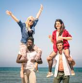 Multiracial best friends at beach having fun with piggyback game - Spring summer concept of multi ethnic friendship against racism - Young people playing together outdoors - Soft focus on action scene — Stock Photo