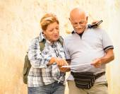 Active senior couple exploring old town of La Valletta with travel map - Concept of youthful elderly and tourist retired lifestyle without age limitation - Warm neutral color tones in cloudy shadow — Stock Photo
