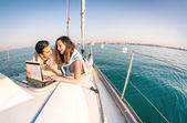 Young couple in love on sail boat having fun with tablet - Happy luxury lifestyle on yacht sailboat - Technology interaction with satellite wifi connection - Round horizon from fisheye lens distortion — Stock Photo