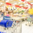 Blurred defocused grocery supermarket - Consumerism concept in period of economic crisis - Bright vivid blur of people in commercial center - Shallow depth of field with focus on shopping cart edge — Stock Photo #72664563