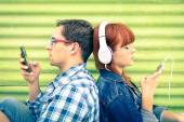 Hipster couple in disinterest moment with mobile phones - Concept of apathy sadness and isolation using new technologies - Boyfriend and girlfriend with smartphones addiction - Vintage filtered look — Stock Photo