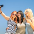 Happy girlfriends taking selfie against blue sky - Friendship summer concept with new trends and technology - Best friends enjoying moments with modern smartphone - Warm sunny afternoon color tones — Stock Photo #72699063