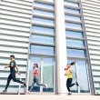 Group of young people running in modern urban area - Fitness girls running with male trainer coach in the city - Sport concept with friends jogging in business center downtown in a sunny bright day — Stock Photo #72699057