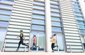 Group of young people running in modern urban area - Fitness girls running with male trainer coach in the city - Sport concept with friends jogging in business center downtown in a sunny bright day — Stock Photo
