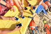 Group of multiracial friends having fun together with smartphone - Closeup of mixed hands social networking with mobile smart phone in sunny day - Technology concept in summer beach everyday lifestyle — Stock Photo