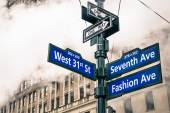 Modern street sign and vapor steam in New York City - Urban concept and road traffic directions in Manhattan downtown - American world famous capital destination on dramatic desaturated filtered look — Stock Photo