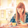 Vintage filtered portrait of serious pensive young woman with smartphone - Hipster girl using mobile smart phone while drinking coffee - Concept of human emotions - Soft focus on sad worried face — Stock Photo #72846629