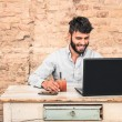 Young hipster guy with mustache sitting at vintage desk with laptop computer in grunge alternative office - Concept of start up business enjoying working hours - Soft retro desaturated filtered look — Stock Photo #73233917