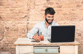 Young hipster guy with mustache sitting at vintage desk with laptop computer in grunge alternative office - Concept of start up business enjoying working hours - Soft retro desaturated filtered look — Stock Photo