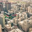 Close up detail of skyscrapers the business district of Johannesburg - Aerial view of modern buildings of the skyline in South Africa biggest city with southafrican flag painted on structure walls — Stock Photo #73335017