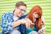 Happy young couple having fun with smartphone at vintage grunge location - Concept of friendship with hipster best friends interacting with new technologies - Beginning moments of a love story — Stock Photo