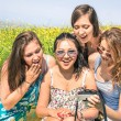 Multiracial girlfriends at countryside picnic watching photos in snapshot instant digital camera - Happy friendship fun concept with young people and new technology trend - Sunny afternoon color tone — Stock Photo #75655155