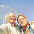 Happy retired senior couple taking selfie at travel around the world - Concept of active playful elderly with mobile phone - Mature people fun lifestyle in sunny day with strong sunlight color tones — Stockfoto #75655241