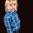 Solemn little boy against a dark background — Stock Photo #62839407