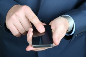 Businessman holding  and using the  mobile  smart  phone — Stockfoto