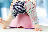 Children's legs hanging down from a chamber-pot — Stock Photo