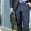 Businessman walking and holding  a  leather briefcase in his han — Stock Photo #59746275