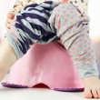 Children's legs hanging down from a chamber-pot — Stock Photo #63215895