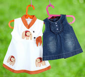 Fashion baby dresses hanging on a hanger on a  green background — Stock Photo